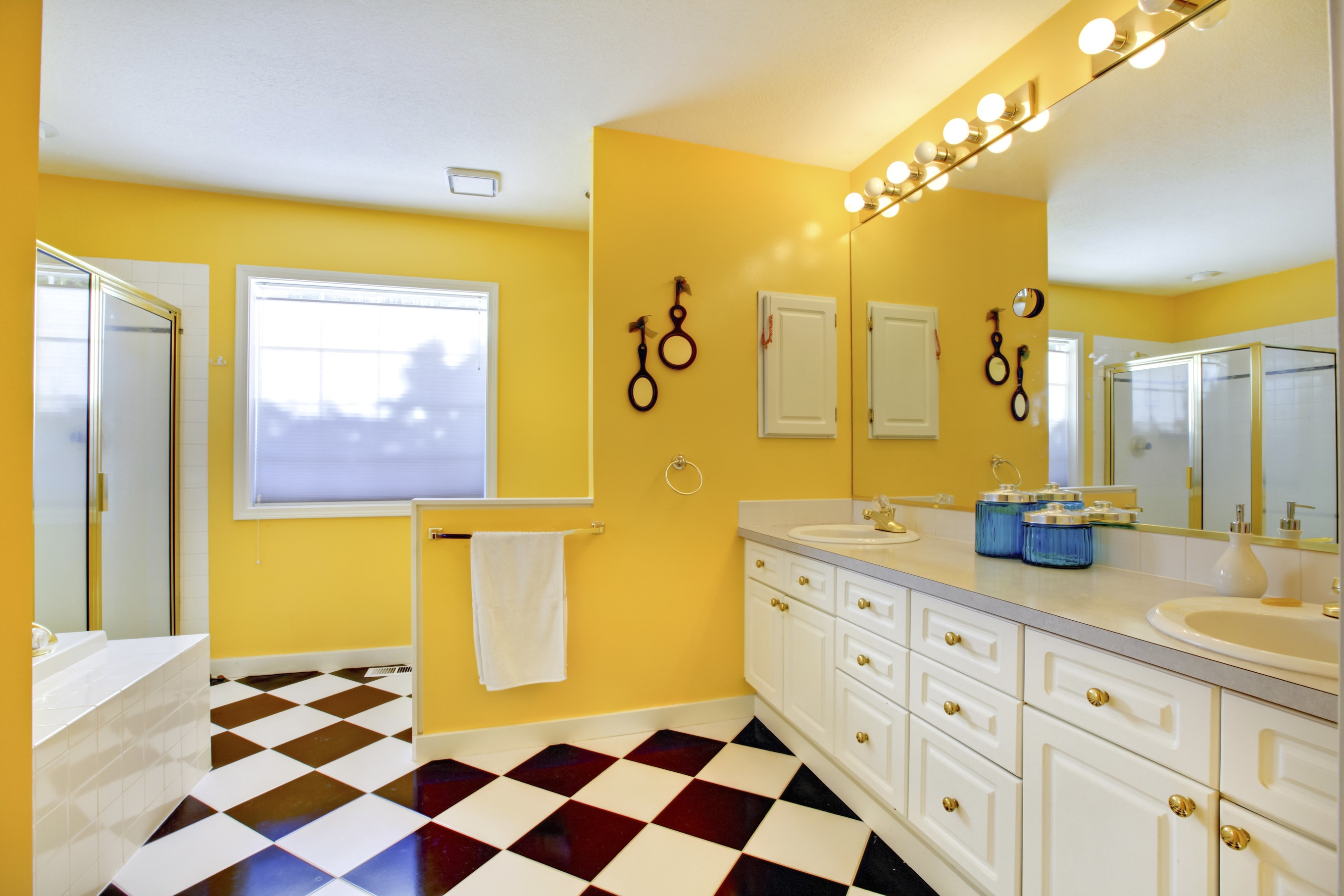 Bright yellow bathroom interior with white cabinets, tile.