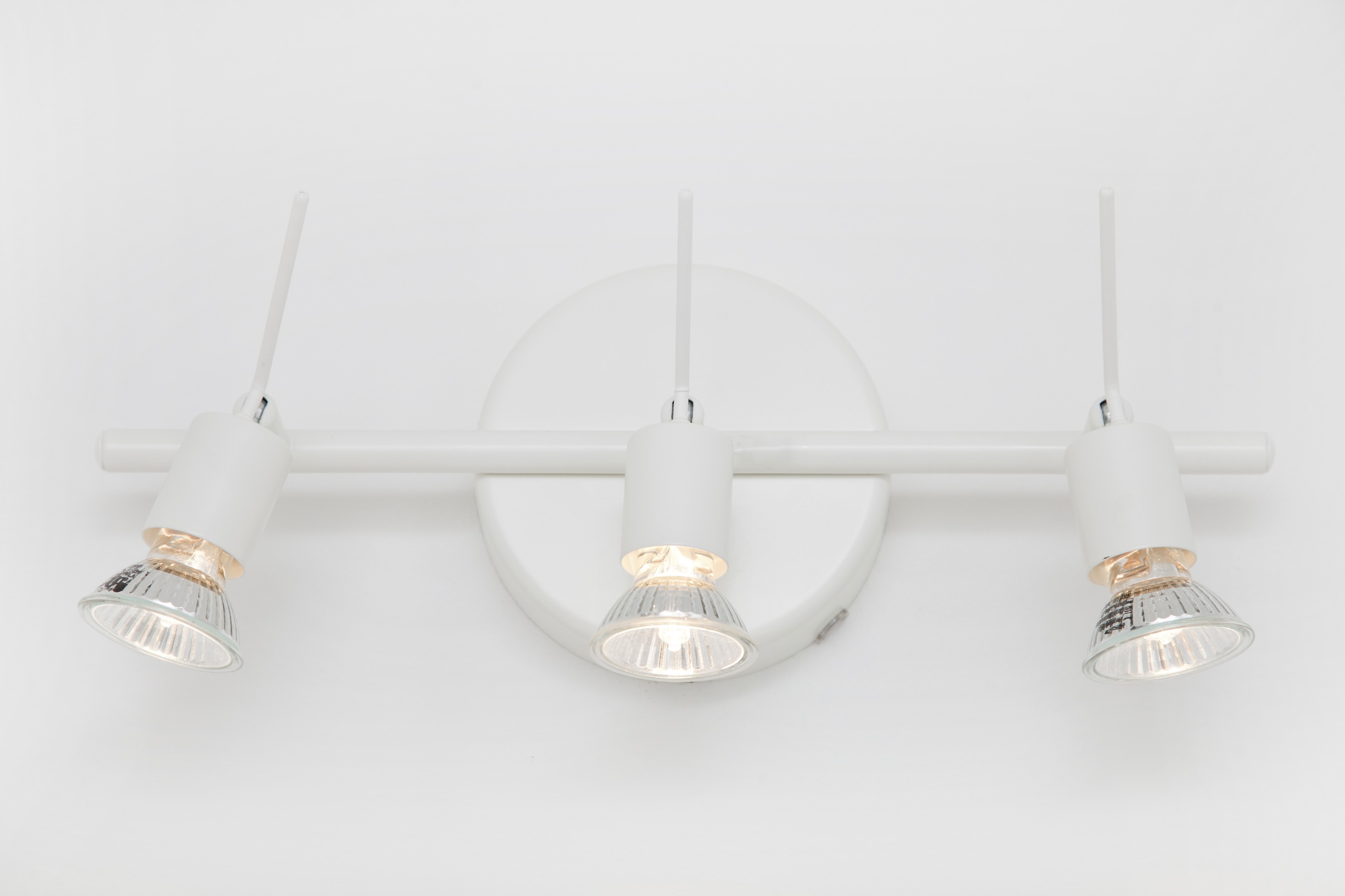 Modern white wall-mounted bathroom light fitting with three adjustable spotlights on a white wall