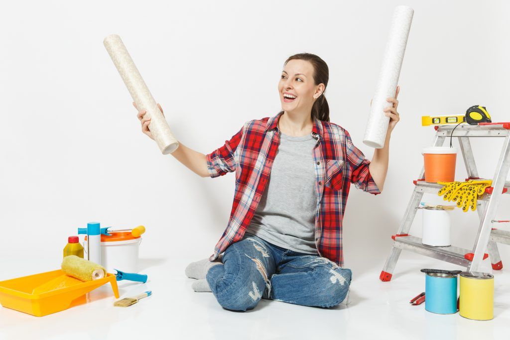 Woman in casual clothes sitting on floor with wallpaper rolls instruments for renovation apartment isolated on white background. Accessories for gluing painting tools. Repair home concept.