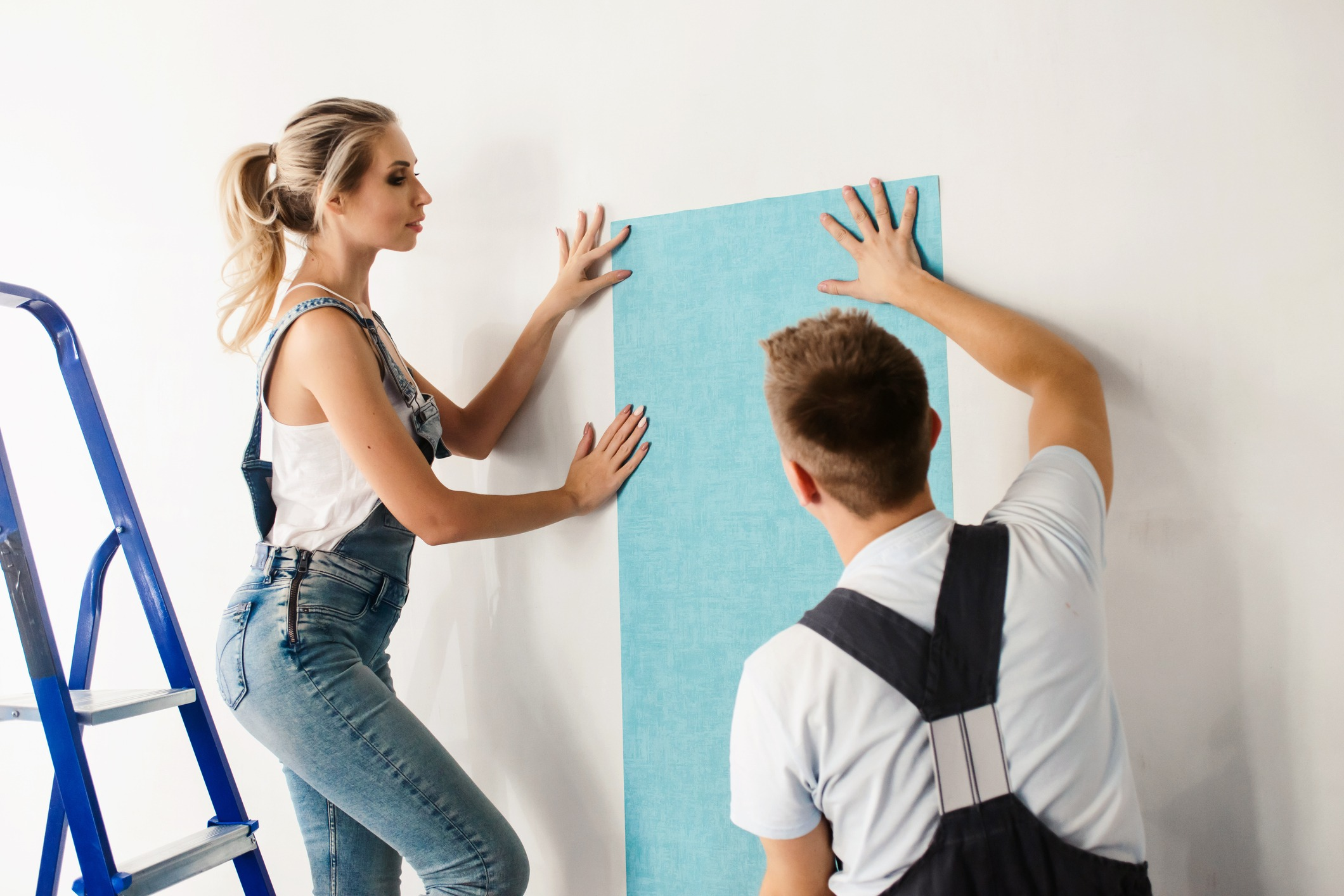Funny couple, woman and her husband wallpapering the walls using a metal ladder. Home renovation and moving to new house concept