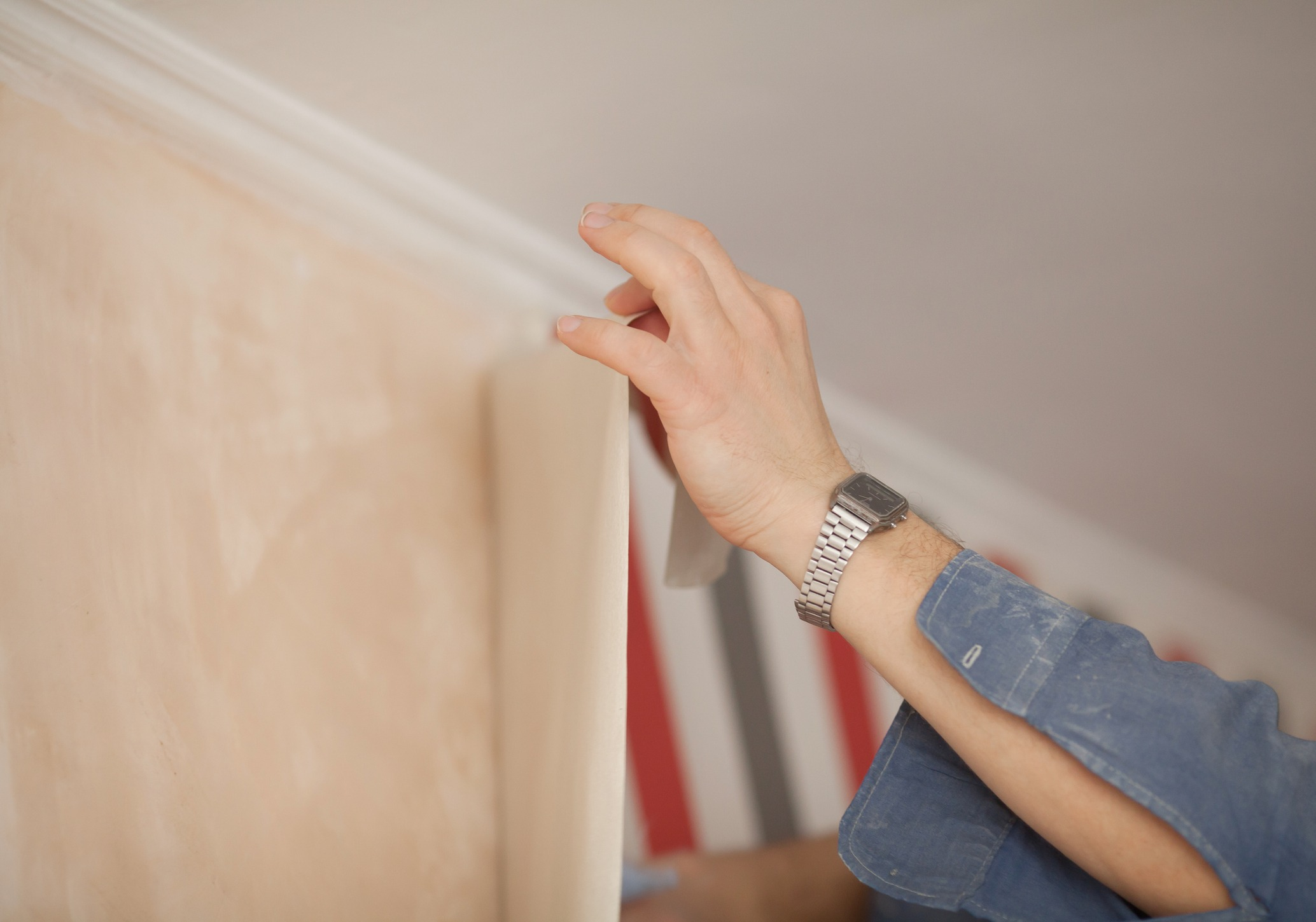 Glueing wallpapers at home. Handyman putting up wallpaper on the wall