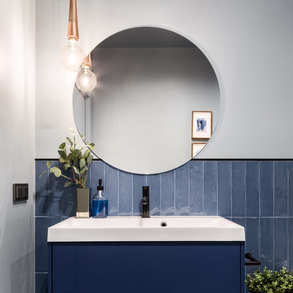 Designed bathroom with stylish blue cabinet, blue wall tiles and big round mirror