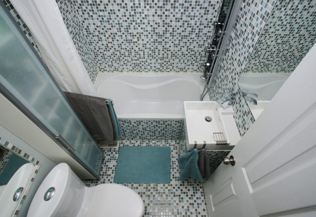 Small, modern bathroom interior. Mosaic tiles. Well organized space. Gray. Blue. White.