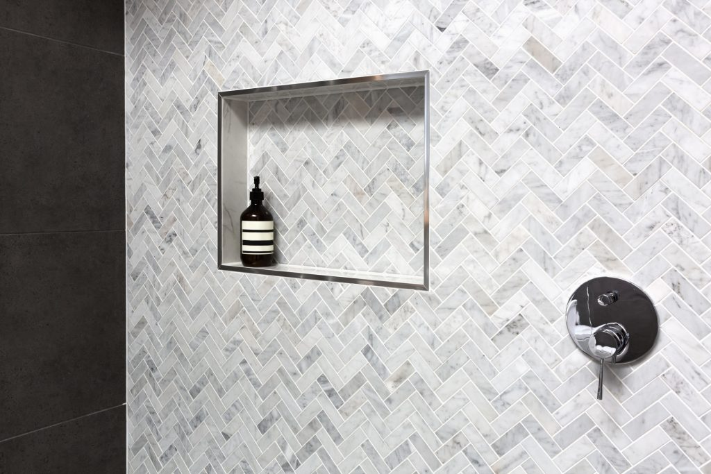 Shower shelf detail in wall of herringbone marble tiles in a luxury new home
